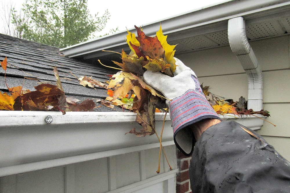 Hand cleaning leafs out of gutters on a house